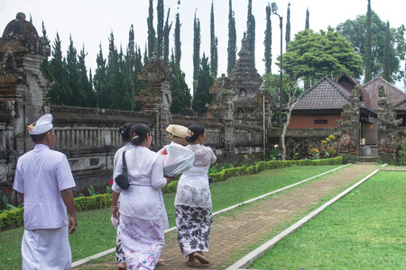 Four Member of Balinese Family Wearing White Clothing Going To Hindu Temple for Praying Bringing Sesajen on The Basket