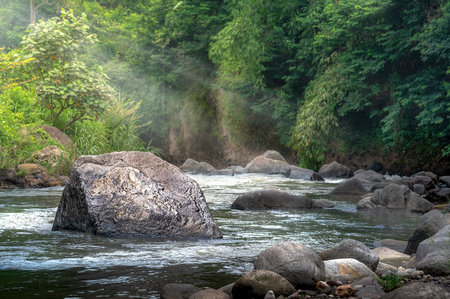 Deep Forest Stream Water Rushing by Big Rock in Middle River at Morning Sunshine and Warm Sunbeam or Sun Ray Through Tropical Forest Tree. Concept of Divine Harmony with Environment 免版税图像