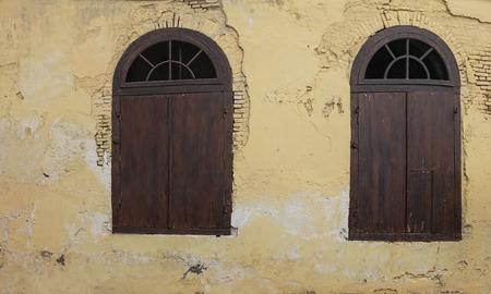 Old Wooden Half Circle Arched Windows. Dark Wood Half Moon Windows with Cream Pastel Yellow Color Damage Aged Brick Wall Standard-Bild - 121410141