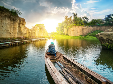 Travel To Future Bright Sunrise by Long Tail Boat on River or Lake Between Rock Cliff For Vacation Travel Trip on Tropical Holiday. Follow Sun Into New Beginning Blue Lake and Being a Captain For HisHer Own Life 版權商用圖片