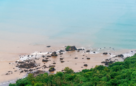 Rocky Soft Pastel Blue Beach Near The Forest. Calm and Serenity Blue Coastline Mix with Muddy Sediment Water and Lush Green Virgin Jungle. Tranquility in Difficulties. Palangpang Beach at Global Geopark Ciletuh. 免版税图像