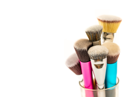 Collection of Cosmetic Foundation Brushes on Glass Jar Container with White Background. Double Fiber Bristle Makeup Foundation Brush. Close Up. Selective Focus. 免版税图像