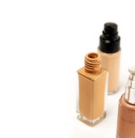 An Open Cap Cosmetic Foundation Bottle on White Background. Liquid Foundation Glass Container. Selective Focus.