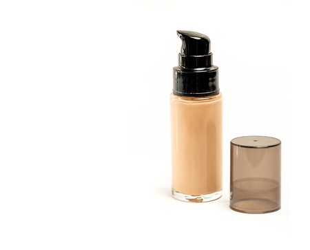 Cosmetic Foundation Bottle with Its Cap Open Beside It on White Backgound and Copy Space for Text or Writing. Selective Focus.
