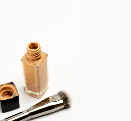 An Open Cosmetic Foundation Bottle with Blur Cap and Brush on White Background. Selective Focus.