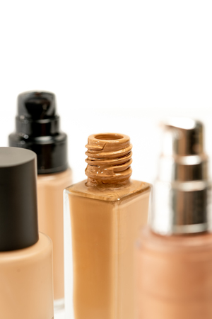 Various Cosmetic Makeup Foundation Bottle on White Background. Liquid Foundation Glass Bottle. Selective Focus. Close Up.