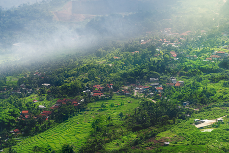 Scenic Vista View of Peaceful Countryside Village with Lush Green Rice Terrace Field on Mountain Slope in Morning Fog During Sunrise Stock Photo