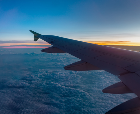 Air Travel Concept. Air Plane Wing Above The Soft Cotton Cloud During Sunrise or Sunset with Blue Sky. Selective Focus. 免版税图像
