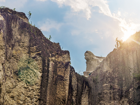Hard Rock Cliff and Blue Cloudy Sky with Sun Light Flaring From Behind The Cliff Standard-Bild - 123491157