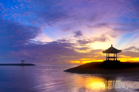 Beachfront Pavilion Silhouette in Sunrise or Sunset Time. Colorful Blue Yellow Sky with Purple Cloud in Morning. Romantic Tropical Pier Pavilion on The Beach with Sun Reflection on Seashore. Standard-Bild - 123491200
