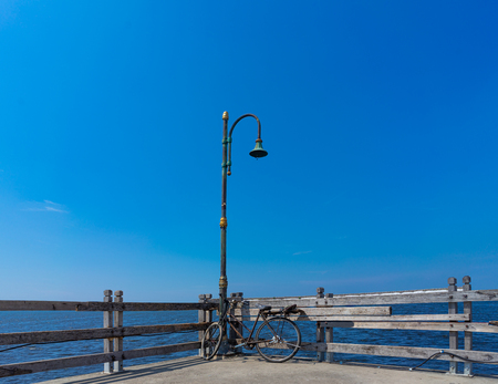 Old Rusty Bicycle Park Under The Damage Lamppost At The Wooden Pier of Marina Beside The Sea. Old Fashioned Classic Bike. Concept of Journey, Travelling and Touring. Stock Photo