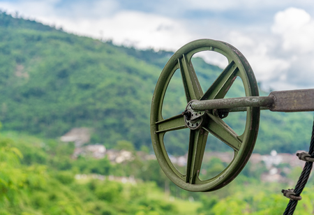 Green Pulley Wheel on the Shaft with Blur Mountain and Sky in Background. Standard-Bild - 123492019