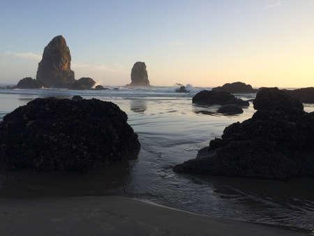 crashing: Waves crashing on Canon Beach Oregon at sunset.