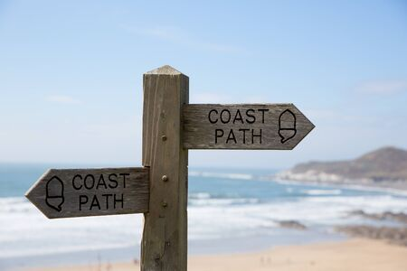 rambling: Coast path sign against sea and sand background