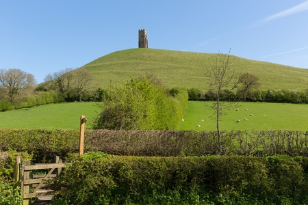 legend: Somerset Glastonbury Tor England, which features the roofless St  Michael s Tower  It is a Scheduled Ancient Monument at the location believed by some to be the Avalon of King Arthur legend
