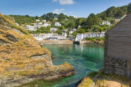 View from rocks to Polperro fishing village harbour Cornwall England UK photo