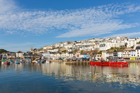 Brixham harbour Devon with houses on the hillside and red colourful boats moored on a still summer calm summer day with blue sky, traditional English coast scene  Stock Photo