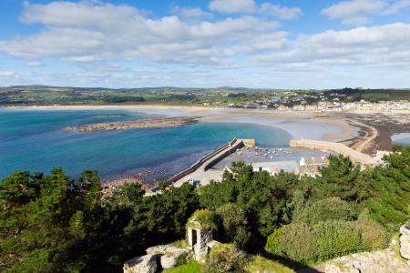 Marazion Cornwall England from St Michaels Mount castle and church with the harbour wall, boats and causeway mainland on a beautiful sunny summer day photo