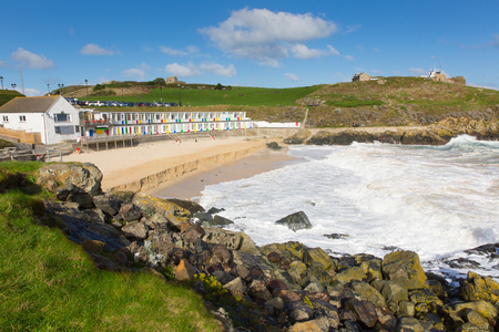 Porthgwidden beach St Ives Cornwall England with colourful beach huts, waves and blue sea and sky
