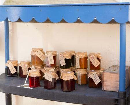 honestidad: Mermeladas caseras y conservas en venta en macetas con etiquetas y caja de honestidad para el pago Foto de archivo