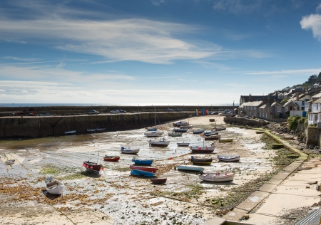 mousehole: Mousehole harbour Cornwall England UK Cornish fishing village with blue sky and clouds