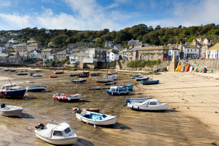 mousehole: Boats in Mousehole harbour Cornwall England Cornish fishing village with blue sky and clouds at low tide Stock Photo