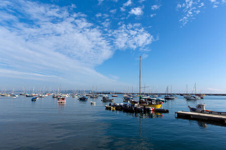 Boats by the yacht club Brixham harbour Devon England UK on a calm summer day with blue sky