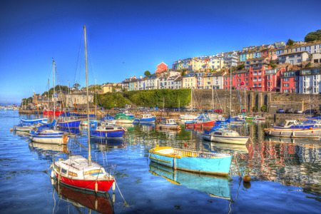 Colourful boats in marina in calm sea with blue sky in HDR houses on hillside