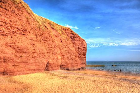warren: Red rock beach Dawlish Warren Devon England with blue sea and sky on a summer day  Stock Photo