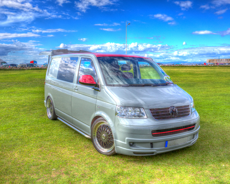 mini bus: Volkswagen VW T5 van alloy wheels and blue sky in HDR Editorial
