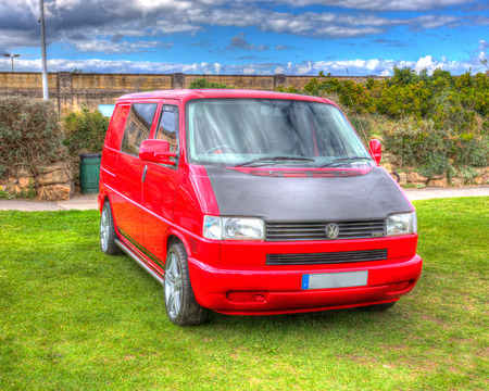 Red Volkswagen VW T4 van alloy wheels and blue sky in HDR Editorial