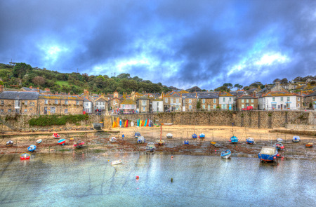 mousehole: Beautiful Cornish village of Mousehole harbour Cornwall England Cornish fishing village with blue sky and clouds at low tide in HDR