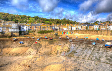 mousehole: Mousehole harbour boats Cornwall England Cornish fishing village with blue sky and clouds at low tide in HDR