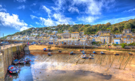 mousehole: Colourful Boats in Mousehole harbour Cornwall England Cornish fishing village with blue sky and clouds at low tide in HDR