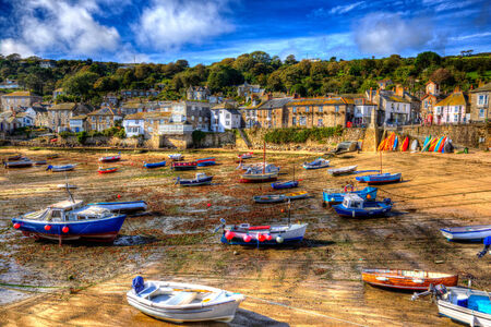 mousehole: Boats in Mousehole harbour Cornwall England Cornish fishing village with blue sky and clouds at low tide in HDR