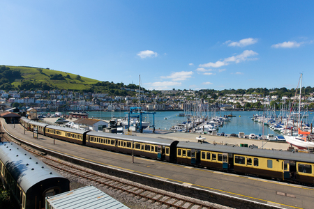 Dartmouth and Kingswear train station with colourful yellow carriages on railway track by marina with boats with blue sky and clouds in Devon England UK
