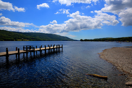 lake district england: Coniston Water Lake District England uk with jetty and blue sky and white clouds on a summer day Stock Photo