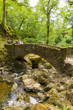 Tourists at Aira Force waterfall in Ullswater Valley Lake District, Cumbria, England in beautiful woodland with bridge