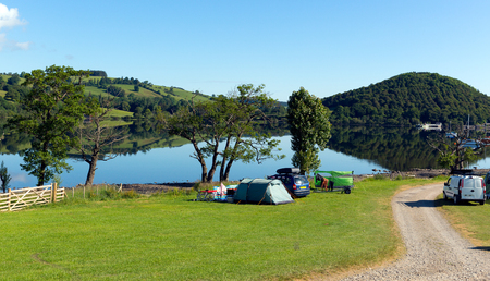 Campsite tents at Ullswater Valley Lake District, Cumbria, England with mountains and blue sky on beautiful calm sunny summer day photo