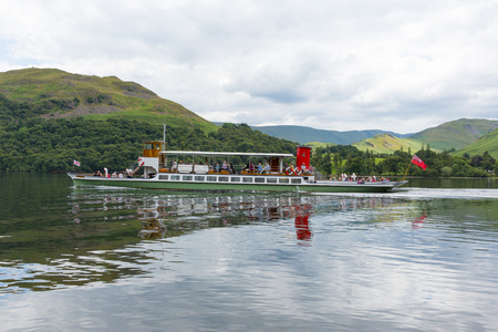 Steam ferry with tourists in Ullswater Valley Lake District, Cumbria, England with green hills