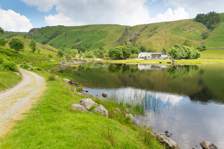 Watendlath Tarn Lake District Cumbria England between the Borrowdale and Thirlmere valleys close to Derwent Water on a calm still summer day
