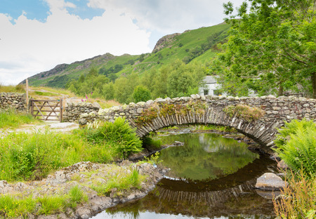 borrowdale: Packhorse bridge Watendlath Tarn Lake District Cumbria England between the Borrowdale and Thirlmere valleys close to Derwent Water on a calm still summer day Stock Photo