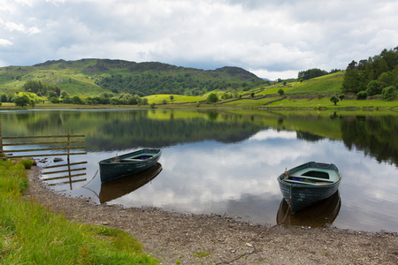 Boats on Watendlath Tarn Lake District Cumbria England between the Borrowdale and Thirlmere valleys close to Derwent Water on a calm still summer day
