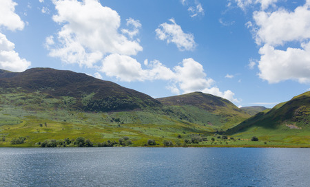 cumbria: Mountains Crummock Lake District North West England UK between Buttermere and Loweswater on summer day with blue sky and white clouds