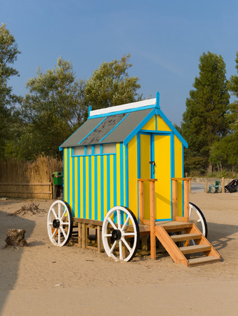 changing room: Seaside changing room bath car hut with wooden wheels in yellow and blue brightly coloured Stock Photo