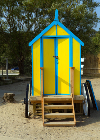 Seaside changing room bath car hut with wooden wheels in yellow and blue brightly coloured photo