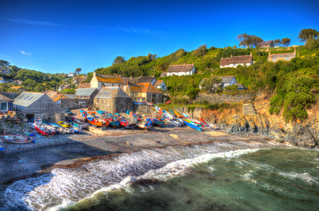 south west england: Cadgwith Cornwall fishing village on the Lizard Heritage coast South West England on a sunny summer day with waves like painting in HDR with blue sky