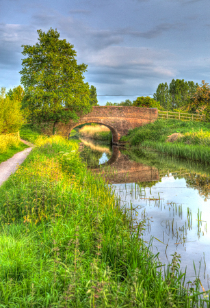 like english: UK canal in English countryside with bridge and footpath on calm still day like painting in HDR