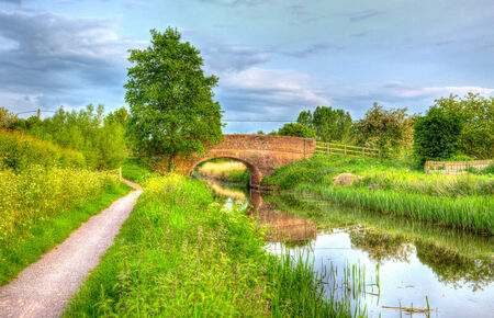 county somerset: Canal with bridge in English countryside on calm still day with footpath in Somerset county