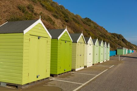 beach huts: Green beach huts in a row with blue sky traditional English structure and shelter found at the seaside